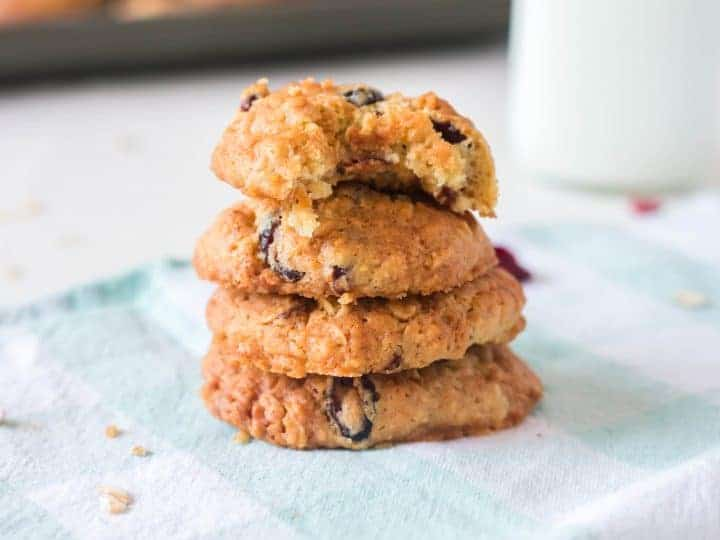 Oatmeal cookies with almond flavoring and cherries stacked up with milk in the background.