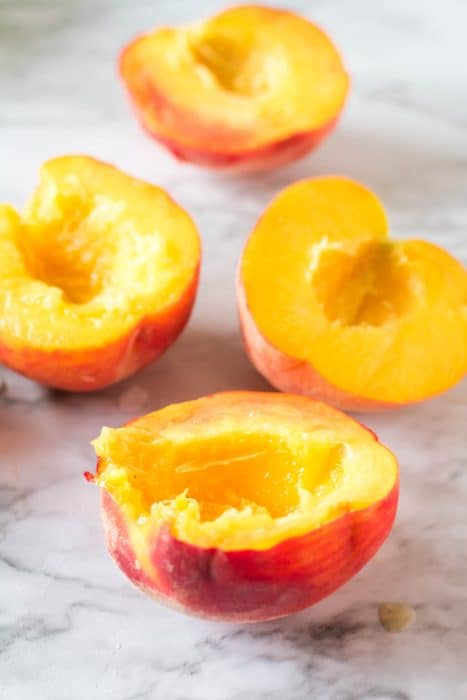 Peach halves with the pits removed on a white marbled background