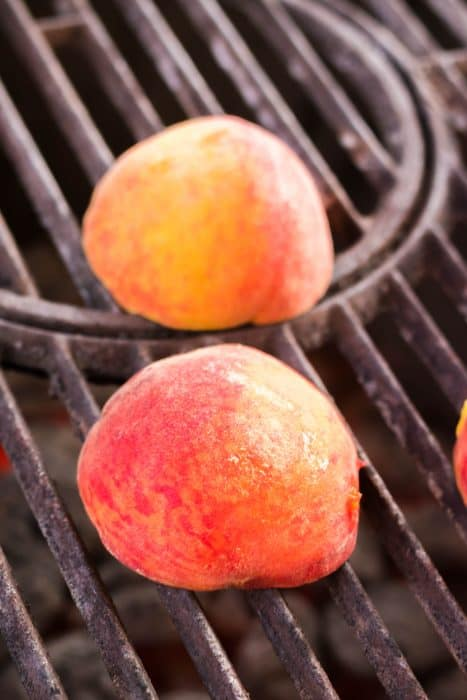 Two peach halves turned upside down on a grill to be roasted.