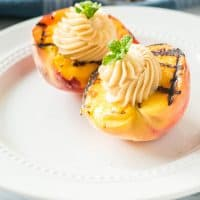 Grilled peaches with cinnamon honey butter on a white plate.