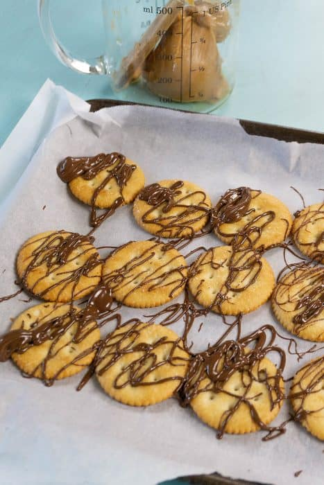 Ritz crackers with peanut butter and chocolate drizzled on them.