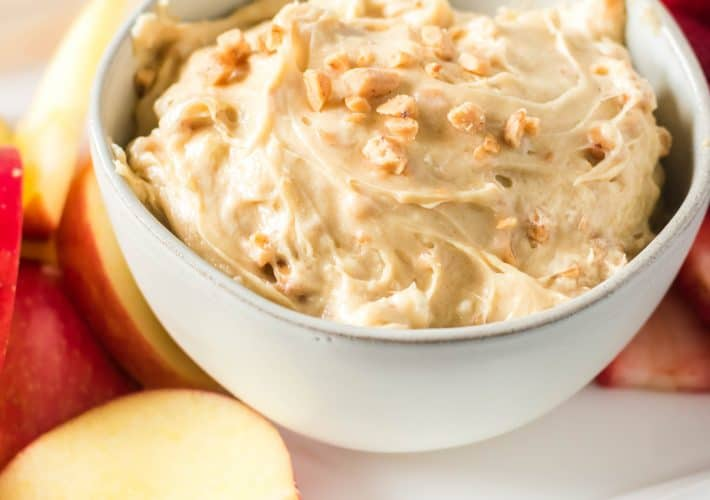 Toffee fruit dip in a white bowl and apples.