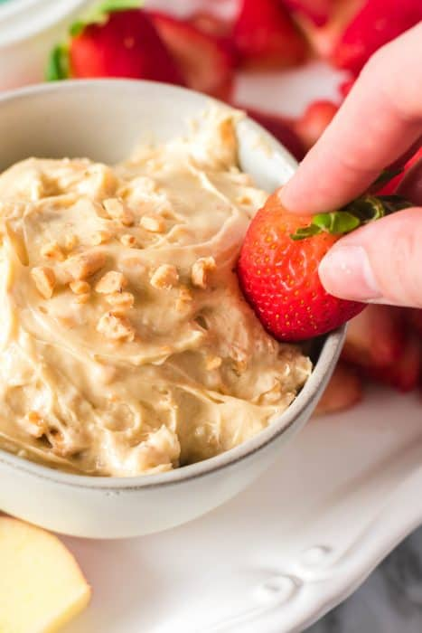 Cream cheese fruit dip with toffee bits in a white bowl and strawberries.