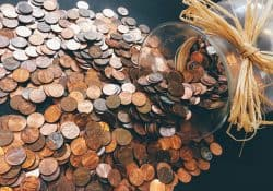 Loose pennies being scattered from a vase.