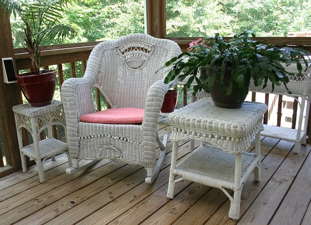 wicker rocking chair with a potted plant out on the deck