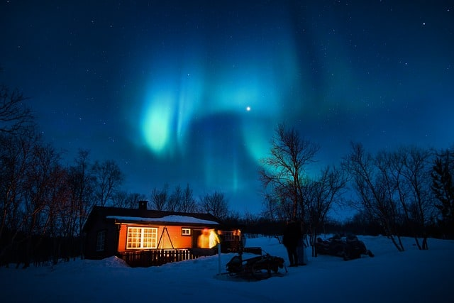 A cabin with snowmobiles out front in winter with the Northern Lights shining overhead.
