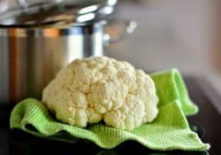A head of raw cauliflower on a green hand towel with a silver stock pot in the background.