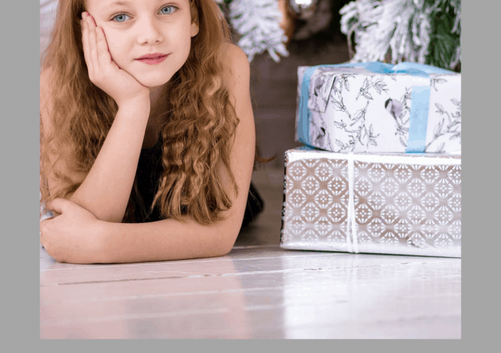 A girl next to a tree with presents with the title 7 money lessons to teach your growing child.