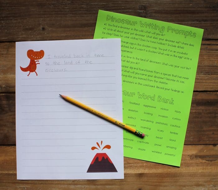 Printable dinosaur writing prompts printed on white and green paper, with a pencil laid across them.