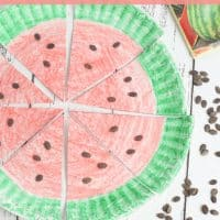 A paper plate colored to look like a watermelon with a green rim and red inside, with watermelon seeds on the plate.