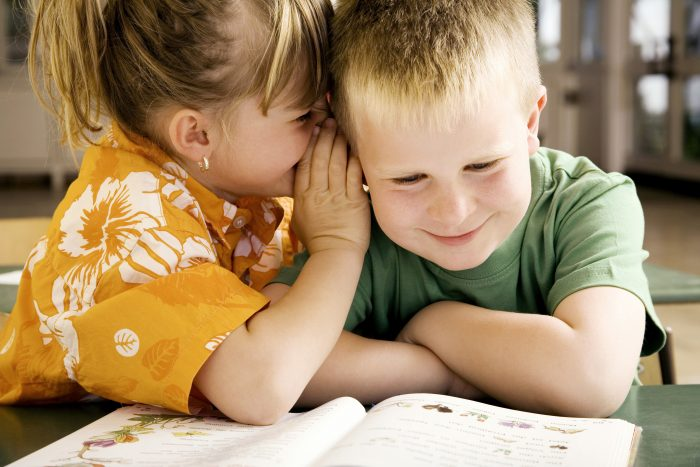A young girl whispering into a young boys ear.