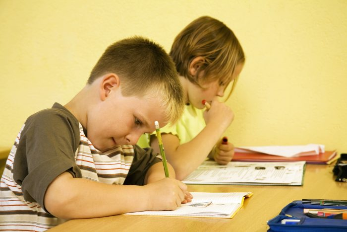 Two kids working on school work at a table.