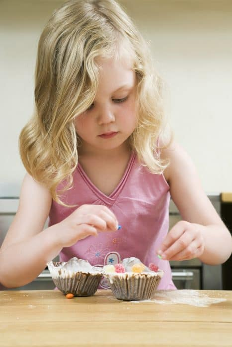 Young child adding coconut to the top of cupcakes.