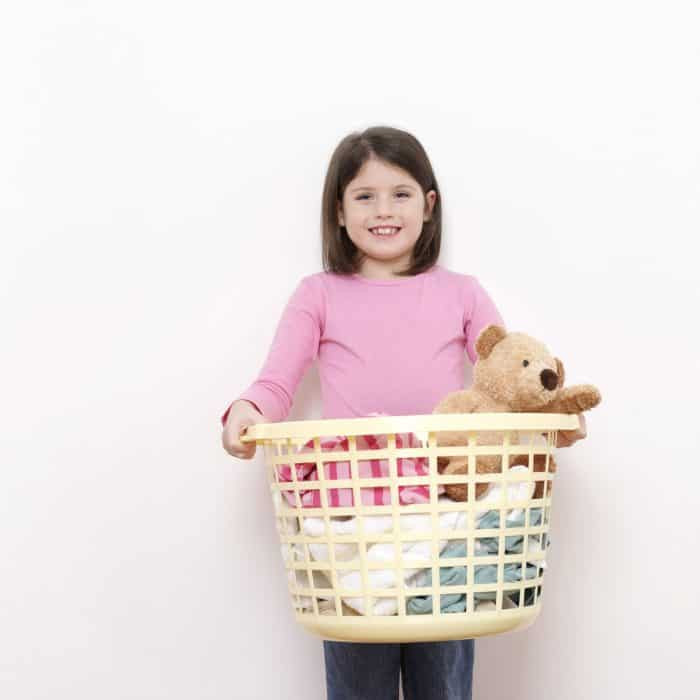 A child holding a laundry basket with a teddy bear in it.