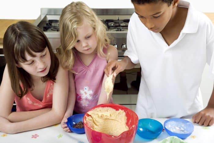 3 kids baking in the kitchen with a red bowl and blue measuring cups.