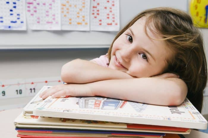 A child with her head on her desk on top of school books.