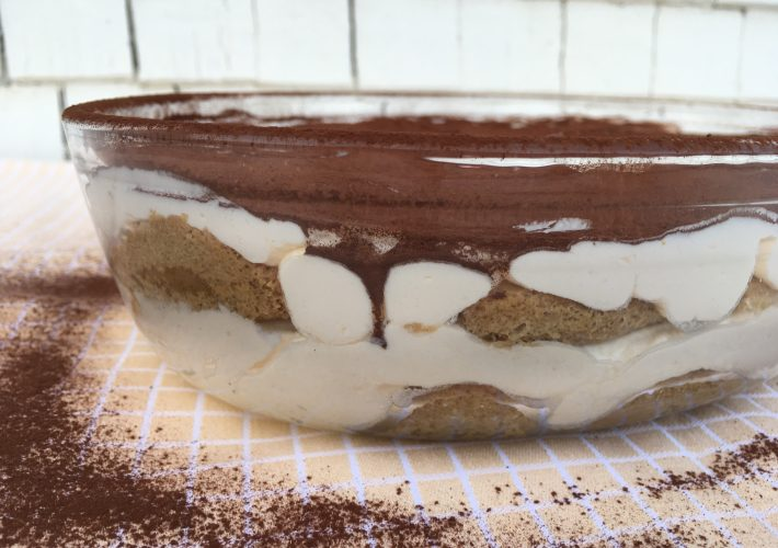 Traditional tiramisu in a glass bowl, featuring chocolate powder sprinkled on top.