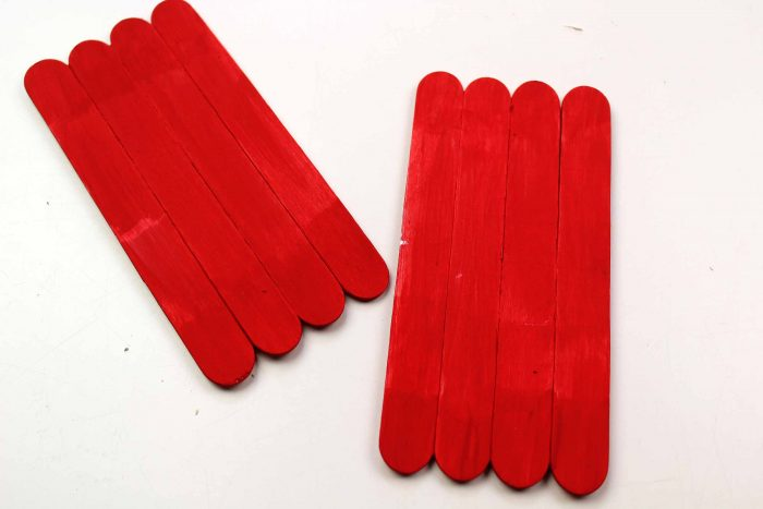 Popsicle sticks painted red and glued together to make a DIY Christmas ornament with the kids.
