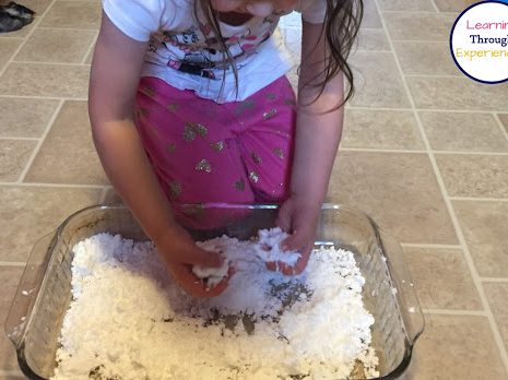 Young girl playing with fake snow in a pyrex baking dish.