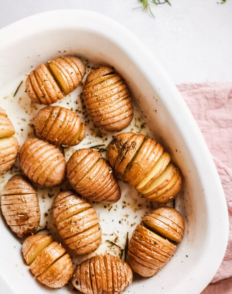 Rosemary Butter Hasselback Potatoes in a white baking dish.